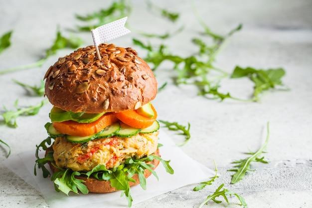 Wegański burger z kotletem warzywnym, batatem, awokado, ogórkiem i rukolą, miejsce. koncepcja zdrowej żywności opartej na roślinach.