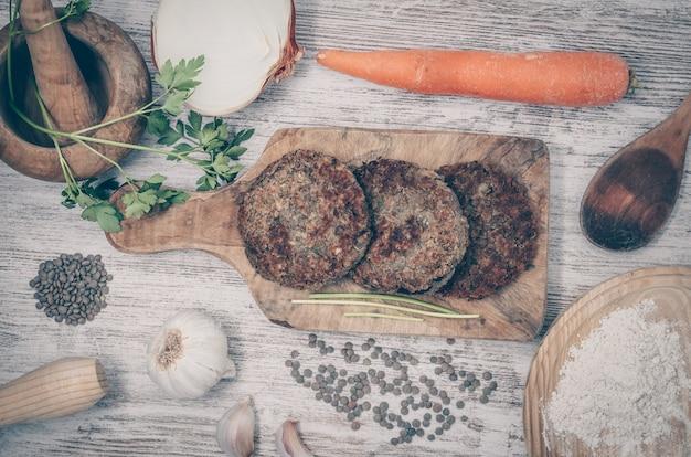 Wegański burger z soczewicą. zdrowe danie wegańskie. drewniane tła