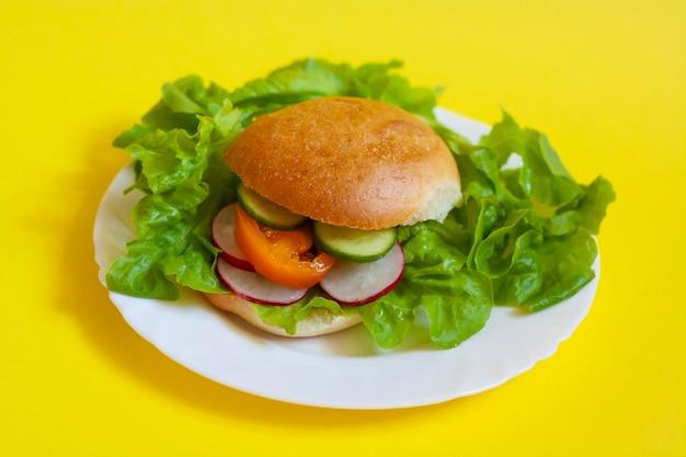 Wegański burger z warzywami na białym talerzu na żółtym tle