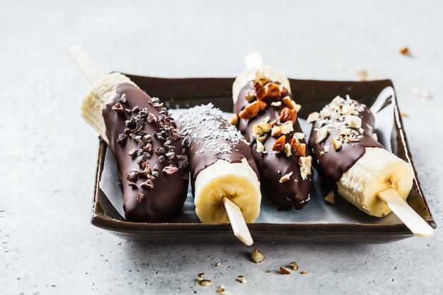 Wegański deser dla dzieci. banan w ciemnej czekoladzie z orzechami.