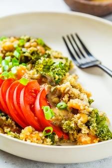 Wegański gulasz z ciecierzycy, słodkich ziemniaków i świeżego pomidora na białym talerzu.