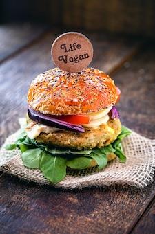 Wegański hamburger, na drewnianym znaku z napisem po angielsku vegan life