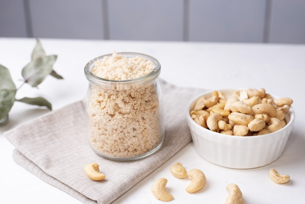 Wegański ser parmezan z surowych zmielonych orzechów nerkowca w szklanym słoju i orzechów nerkowca na białym tle, wegetariańskie jedzenie, z bliska.