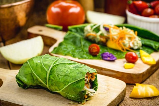 Wegański wrap z jarmużu lub liści sałaty, nadziewany różnymi warzywami, zdrowy fast food