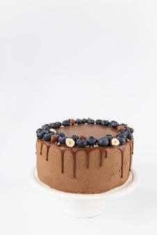Wegańskie ciasto czekoladowe z jagodami, orzechami laskowymi i dripa na jasnym tle
