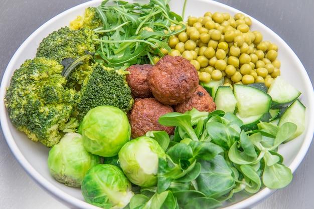 Wegańskie danie z klopsikami sojowymi i zielonymi warzywami
