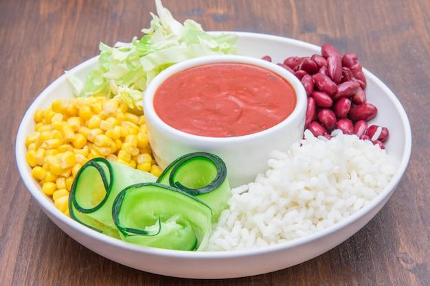 Wegańskie danie z ryżem, czerwoną fasolą, kukurydzą i ogórkiem