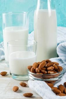 Wegańskie jedzenie alternatywne, migdałowe mleko niemleczne na jasnoniebieskim tle, miejsce