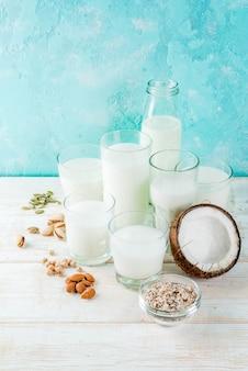 Wegańskie jedzenie alternatywne, zestaw różnych niemlecznego mleka - ryż, kokos, migdały, pistacje, sezam, nasiona dyni, soja, orzechy, płatki owsiane, na jasnoniebieskim tle, miejsce