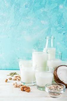 Wegańskie jedzenie alternatywne, zestaw różnych niemlecznego ryżu mlecznego, kokosa, migdałów, pistacji, sezamu, pestek dyni, soi, orzechów, płatków owsianych, na jasnoniebieskim,