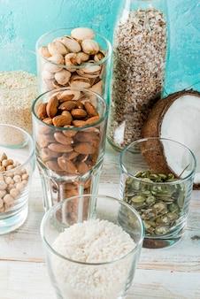 Wegańskie jedzenie alternatywne, zestaw różnych składników do mleka bez mleka, ryżu, kokosa, migdałów, pistacji, sezamu, pestek dyni, soi, orzechów, płatków owsianych, na jasnoniebieskim,