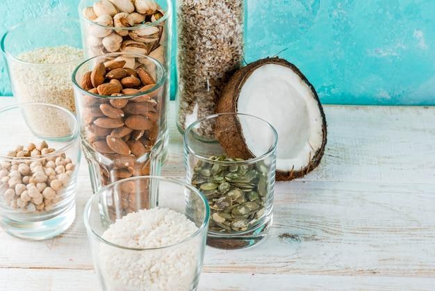 Wegańskie jedzenie alternatywne, zestaw różnych składników mleka niemlecznego - ryż, kokos, migdały, pistacje, sezam, nasiona dyni, soja, orzechy, płatki owsiane, na jasnoniebieskim, copyspace