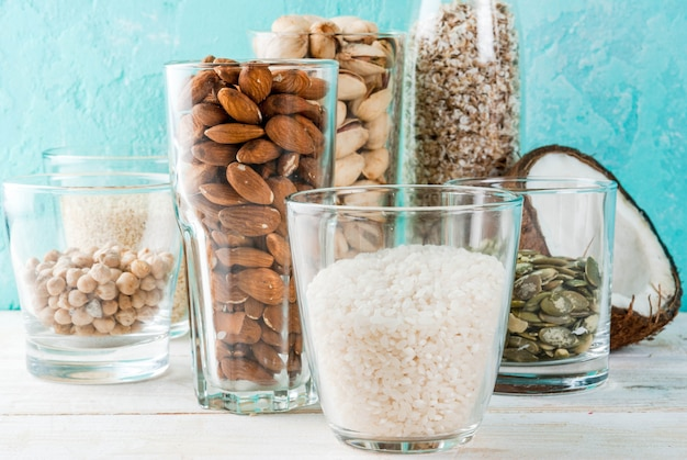 Wegańskie jedzenie alternatywne, zestaw różnych składników mleka niemlecznego - ryż, kokos, migdały, pistacje, sezam, nasiona dyni, soja, orzechy, płatki owsiane, na jasnoniebieskim tle, miejsce