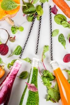 Wegańskie jedzenie dietetyczne. wybór kolorowych świeżych organicznych koktajli napoje z jesiennych warzyw: buraki, dynia, marchew, warzywa liściaste. w butelkach biały stół. skopiuj widok z góry