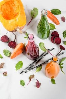 Wegańskie jedzenie dietetyczne. wybór kolorowych świeżych organicznych koktajli napoje z jesiennych warzyw: buraki, dynia, marchew, warzywa liściaste. w butelkach biały stół. widok z góry