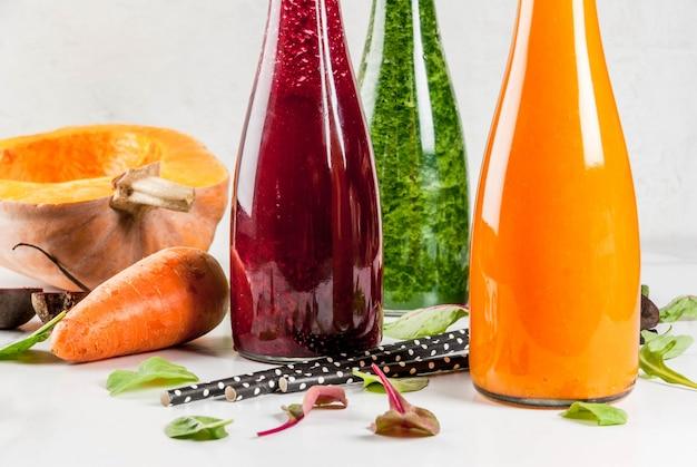 Wegańskie jedzenie dietetyczne. wybór kolorowych świeżych organicznych koktajli warzywnych z jesiennymi warzywami: burak, dynia, marchewka, warzywa liściaste. w butelkach, ze słomkami, biały marmurowy stół. copyspace