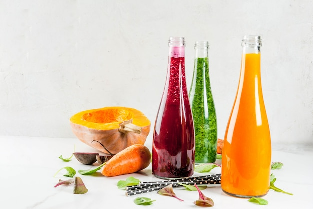 Wegańskie jedzenie dietetyczne. wybór kolorowych świeżych organicznych koktajli warzywnych z jesiennymi warzywami: burak, dynia, marchewka, warzywa liściaste. w butelkach, ze słomkami, biały marmurowy stół. skopiuj miejsce