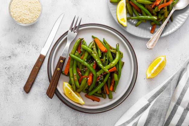 Wegańskie jedzenie. gotowana zielona fasolka szparagowa i marchewka. zdrowa sałatka fasolka szparagowa i marchewki zamyka up.