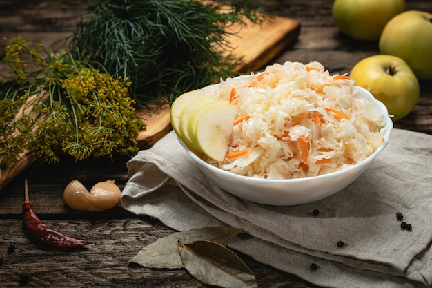 Wegańskie jedzenie - kapusta kiszona z jabłkami na drewnianej powierzchni