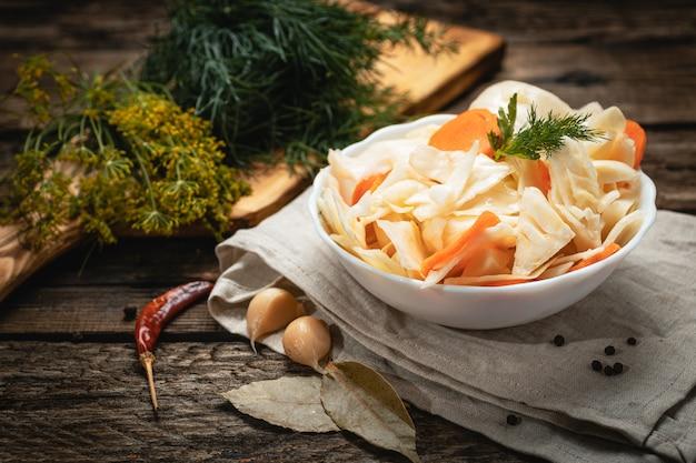 Wegańskie jedzenie - kapusta kiszona z marchewką na drewnianej powierzchni
