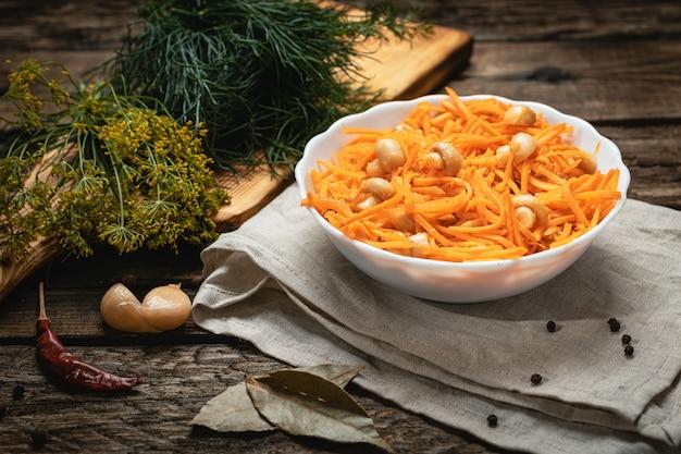 Wegańskie jedzenie - koreańska marchewka z grzybami na drewnianej powierzchni