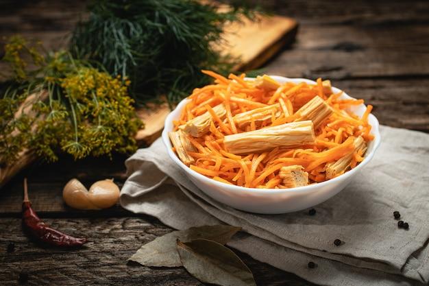 Wegańskie jedzenie - koreańska marchewka ze szparagami na drewnianej powierzchni, eko warzywa