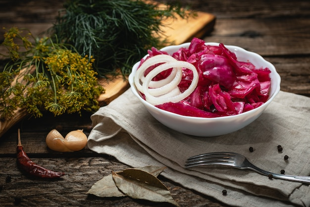Wegańskie jedzenie - marynowana czerwona kapusta z cebulą na drewnianej powierzchni