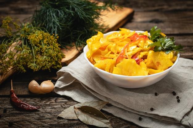 Wegańskie jedzenie - marynowana kapusta z papryką na drewnianej powierzchni