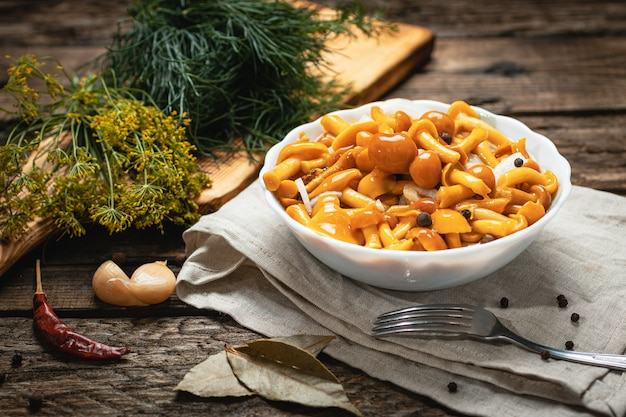 Wegańskie jedzenie - marynowane grzyby z cebulą na drewnianej powierzchni