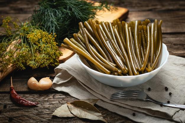 Wegańskie jedzenie - marynowane łodygi czosnku na drewnianej powierzchni