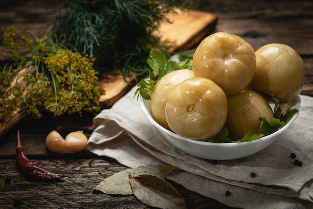 Wegańskie jedzenie - marynowane zielone pomidory na drewnianej powierzchni