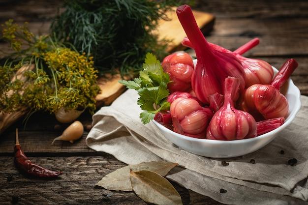 Wegańskie jedzenie - marynowany czerwony czosnek na drewnianej powierzchni