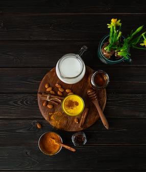Wegańskie kurkumy latte w szklance, mleko migdałowe, przyprawy, doniczkowe żółte duffodils, widok z góry