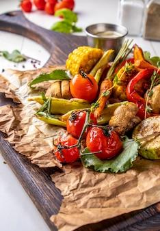 Wegańskie menu grillowe, warzywa z grilla - cukinia, papryka, pomidory koktajlowe, kukurydza, marchew i pieczarki podawane na desce na białej powierzchni, orientacja pionowa