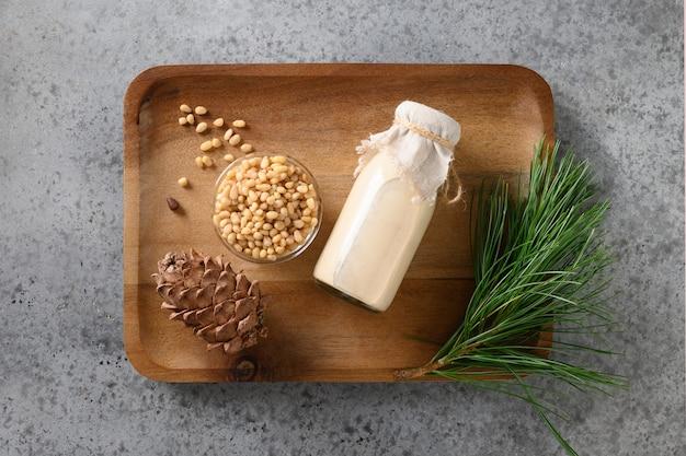 Wegańskie mleko cedrowe w butelce na szarym tle zdrowy wegański napój