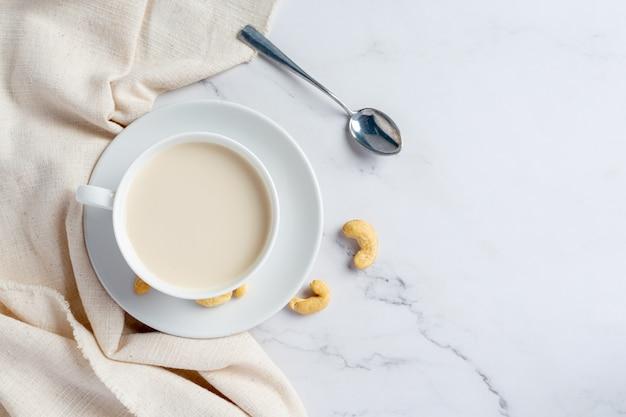 Wegańskie mleko nerkowca w szklance z orzechami nerkowca na marmurowym tle