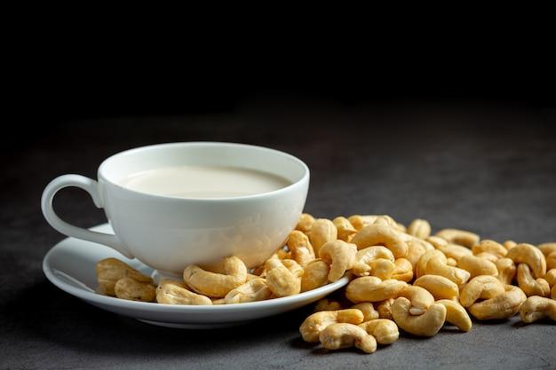 Wegańskie mleko nerkowca w szkle z orzechami nerkowca na ciemnym tle
