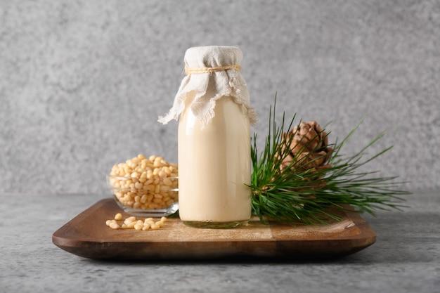 Wegańskie mleko z orzechów cedrowych na szarym tle niemleczne mleko alternatywne