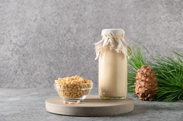 Wegańskie mleko z orzechów cedrowych w butelce na szarym tle alternatywne mleko zdrowy wegański napój