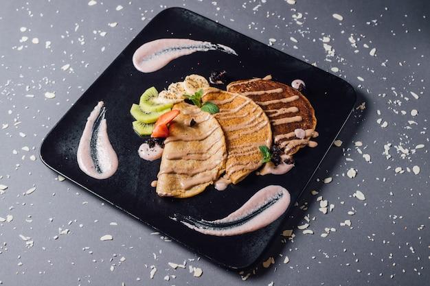 Wegańskie Naleśniki Z Owocami Sezonowymi I Sosem Tofu. Zawiera Mąkę Pszenną, Mleko Roślinne, Słodzone Cukrem Kokosowym. Na Talerzu, Odizolowywającym Na Błękitnym Tle Premium Zdjęcia