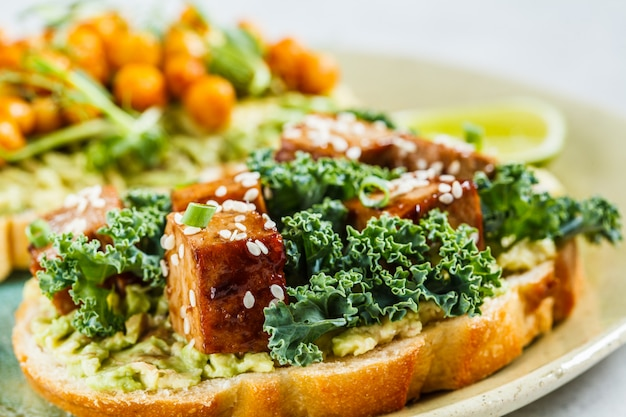 Wegańskie otwarte kanapki z guacamole, tofu, ciecierzycą i kiełkami na talerzu.