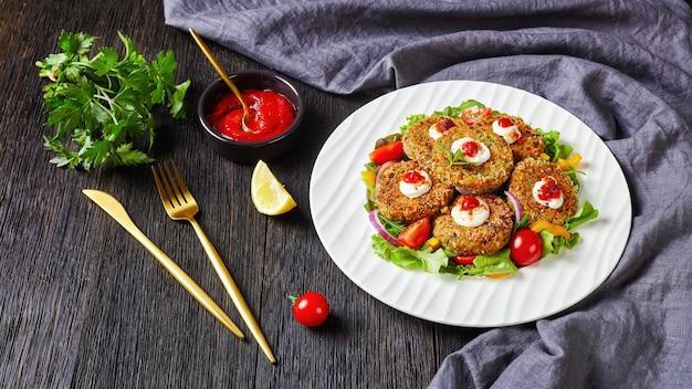 Wegańskie paszteciki z roślin strączkowych, cebuli i zieleniny w panierce z bułki tartej panko podane na białym talerzu ze świeżą sałatą i sosem pomidorowym, widok poziomy z góry