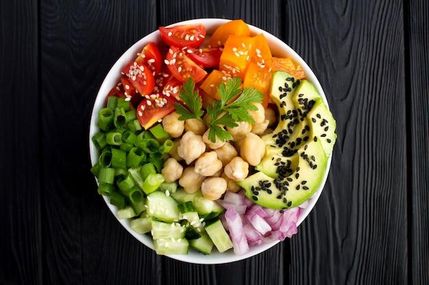 Wegańskie poke miska z ciecierzycy i warzywami w białej misce na środku czarnego drewnianego tła