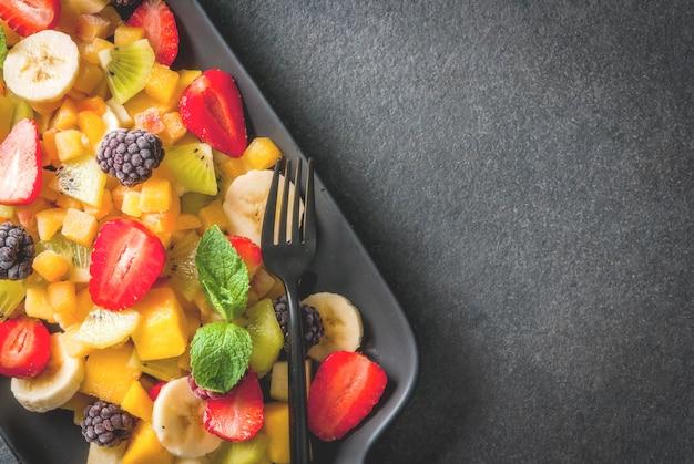 Wegańskie potrawy dietetyczne. witaminy deser. lato. sałatka ze świeżych owoców mango, brzoskwini, jabłka, banana, kiwi, truskawki, jeżyn. na czarnej płycie ceramicznej, czarny kamienny stół widok z góry