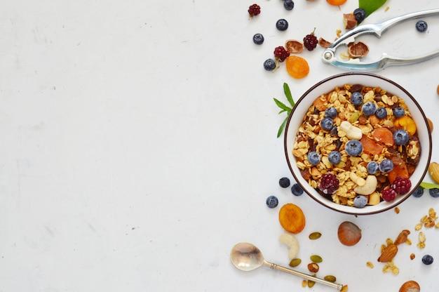 Wegańskie śniadanie ze zdrową żywnością: domowa muesli z orzechami, nasionami i jagodami