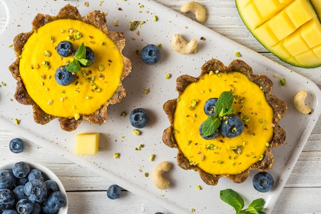 Wegańskie surowe serniki mango ze świeżymi jagodami, miętą i orzechami. koncepcja zdrowego wegańskiego bezglutenowego jedzenia