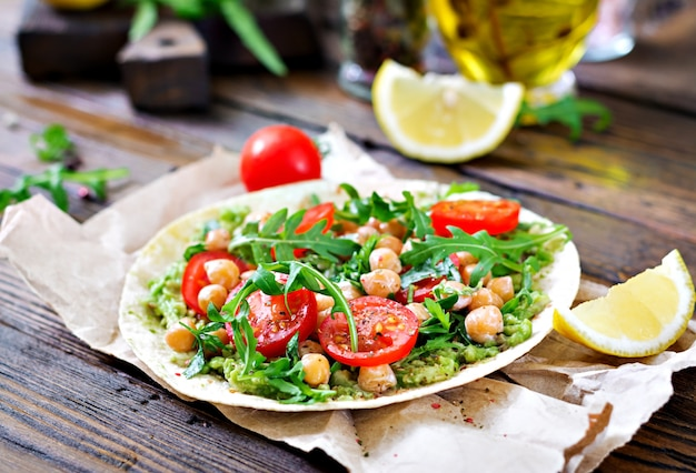 Wegańskie tacos z guacamole, ciecierzycą, pomidorami i rukolą. zdrowe jedzenie. przydatne śniadanie