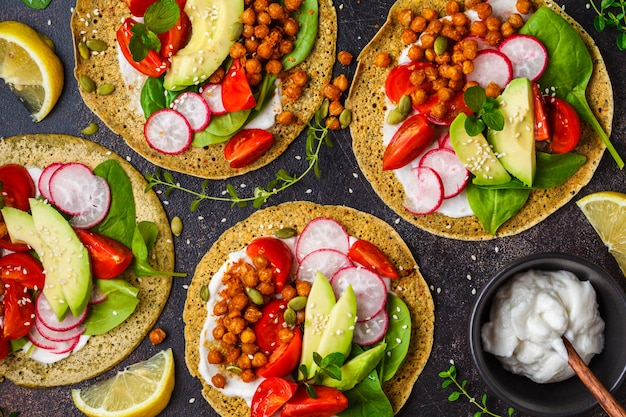 Wegańskie tacos z pieczoną ciecierzycą, awokado, sosem i warzywami, widok z góry.