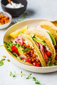 Wegańskie tacos z pieczoną ciecierzycą, awokado, sosem i warzywami.