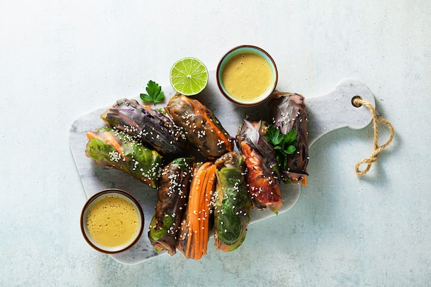Wegańskie tęczowe letnie bułeczki w ryżowym opakowaniu z ostrym sosem migdałowym.